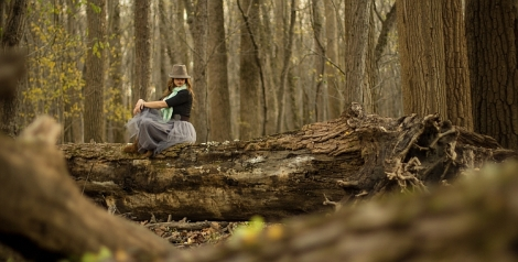 A young woman sitting on a fallen log in a forest