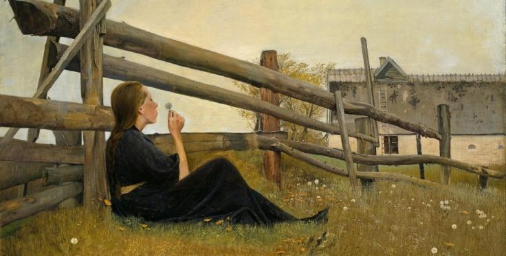 Woman lying in a meadow blowing a dandelion clock